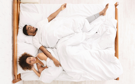Uncomfortable dream. Upset black woman suffering from her sprawled man in bed, top view with empty space