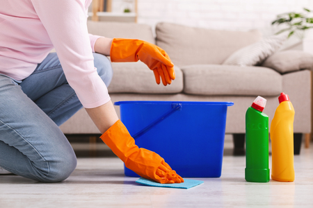 Woman with obsessive compulsive disorder cleaning floor with detergents at home, empty space