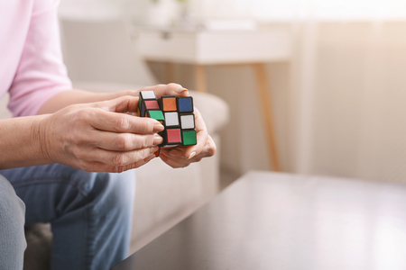 Kharkiv, Ukraine - January 14, 2019: Old woman holding Rubik's cube and playing with it at home, Rubik's cube invented by Hungarian architect Erno Rubik in 1974, free space