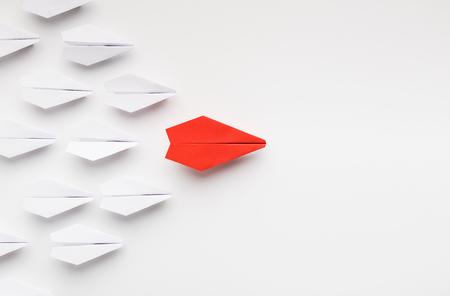 Opinie leiderschap concept. Rood papieren vliegtuig dat een ander leidt en de menigte beïnvloedt, witte achtergrond, bovenaanzicht met vrije ruimte