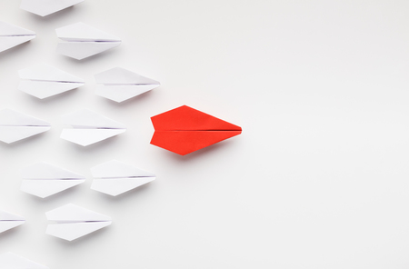 Opinion leadership concept. Red paper plane leading another ones, influencing the crowd, white background, top view with free space