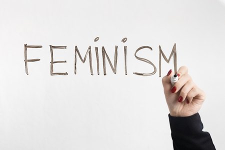 Fight for womens rights. Female hand writing word FEMINISM on glass board, white background, free space Stock Photo