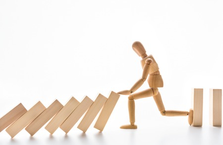 Strength of leader. Wooden mannequin stopping domino effect on white background, free space