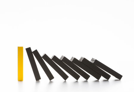 Strength of one. Domino effect stopped by unique strong piece, white background, copy space Archivio Fotografico
