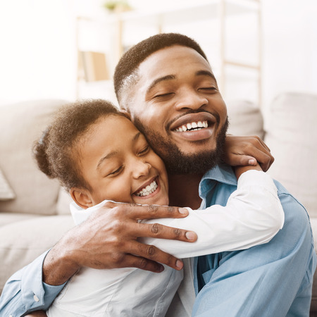 African-american daughter hugging father with love and tenderness at home, crop Stockfoto
