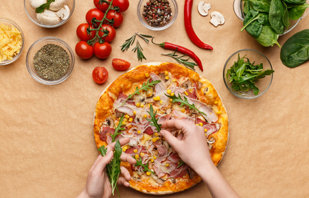 Woman adding rocket salad to pizza, decorating it with various ingrediends, top view Archivio Fotografico
