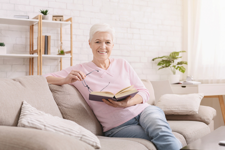 Learning foreign languages. Cheerful senior woman reading educational book at home