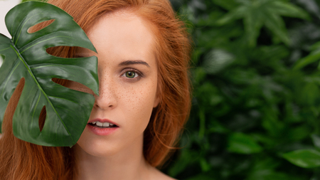 Natural cosmetics and skincare. Portrait of young redhead woman with freckles smiling in tropical leaves. 版權商用圖片