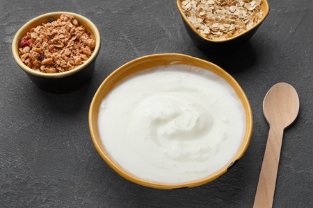 Granola, oat flakes and yogurt in bowls on dark background. Low calorie breakfast concept