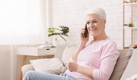 Attractive senior woman chatting on phone, smiling and listening to call, panorama with free space Stock Photo