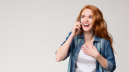 Oh my gosh! Young amazed redhead woman talking on phone, very happy and excited, gray panorama background with free space 版權商用圖片