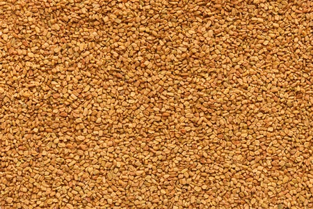 Golden texture of aromatic fenugreek seeds, abstract culinary background