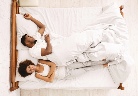 Uncomfortable black woman sleeping by man in bed, top view with free space Stock Photo