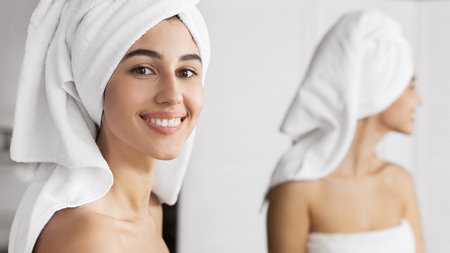 Smiling cute girl with towel on her head standing in front of mirror in bathroom, looking at camera. Pampering and beauty care concept