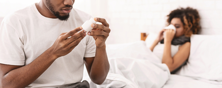 Caring husband treating his sick wife, reading prescription on pills bottle, panorama