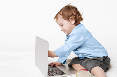Cute baby boy talking with dad on laptop through video call, touching computer screen, miss his daddy, copy space