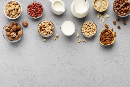 Bowls with various nuts and jars with milk top view. Lactose free milk concept, copy space
