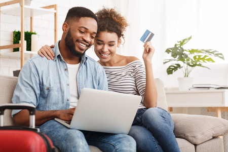 African-american couple booking tour online on laptop, preparing for honeymoon