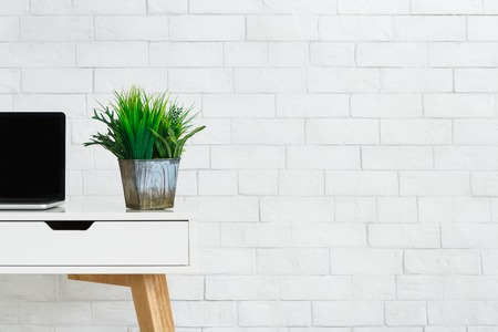 Laptop and box with green home plants composition on desk at white brick wall background, copy space