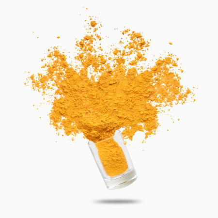 Condiment splash. Yellow turmeric powder flying, isolated on white background 스톡 콘텐츠