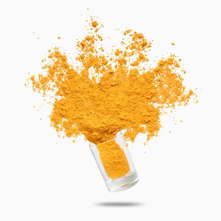 Spruzzata di condimento. Polvere di curcuma gialla volante, isolata su sfondo bianco