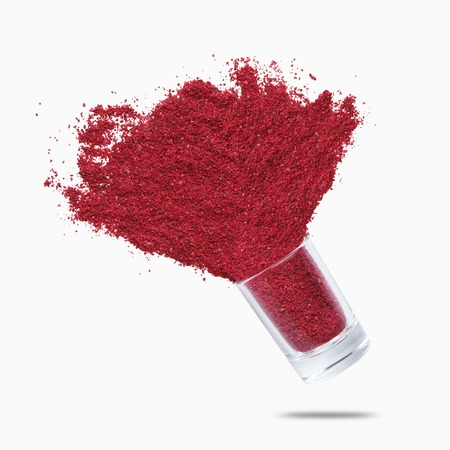 Sumac explosion. Glass jars with oriental spice flying on white background