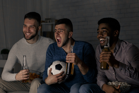 Friends watching football match, cheering for favourite team at home