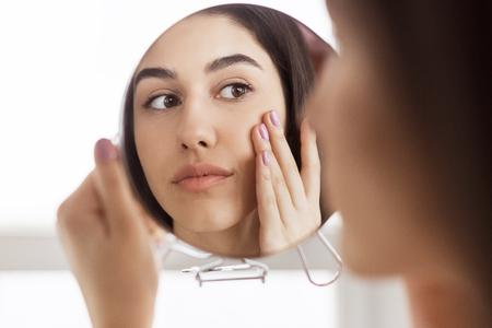 Afro-american girl looking herself in round mirror in bathroom. Eyes wrinkles concept