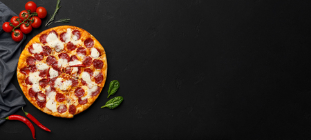 Pepperoni pizza on black background with empty space, top view