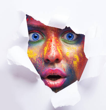 Need more color. Emotional shocked woman with bright creative makeup peeking through hole in white paper, free space.