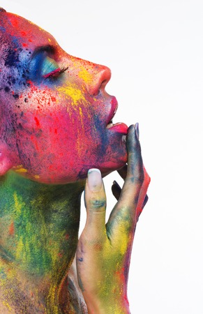 Pure pleasure. Erotical portrait of young woman with colorful art bodypaint, touching her lips with closed eyes, side view