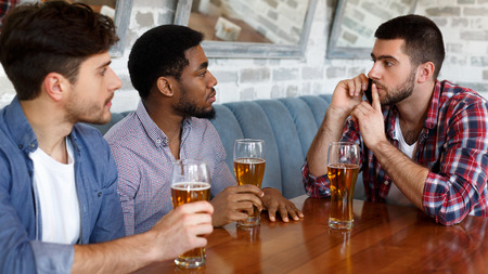 Let me talk on phone. Man asking for silence, sitting in bar with friends
