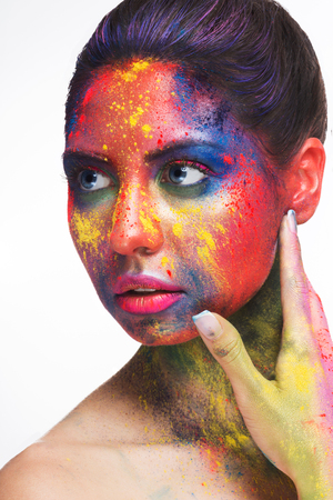 Holi colors festival. Young woman with colorful powder art make-up on white studio background, closeup portrait Stock Photo
