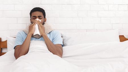 Zieke Afro-Amerikaanse man snuit zijn neus in papieren servet in bed, panorama met vrije ruimte