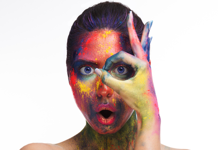 Excited woman with colorful artistic makeup looking through ok gesture, white studio background Stock Photo - 118224915