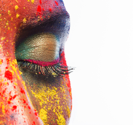 Holi colors festival. Eye of female beauty model with bright colorful powder art make-up on white studio background, closeup