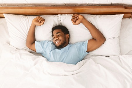 Comfortable sleep. Smiling african-american millennial guy sleeping, sprawled in bed, top view