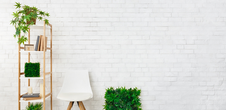 Shelving with house plants and scandinavian chair at white brick wall, copy space. Modern stylish design concept Archivio Fotografico - 118460804