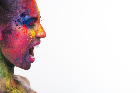 Emotional portrait of girl with bright colorful makeup screaming at free space, white studio background