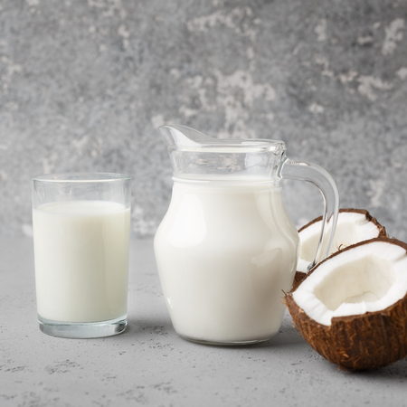 Chopped fresh coconut, jar and glass full of coconut milk on grey background.