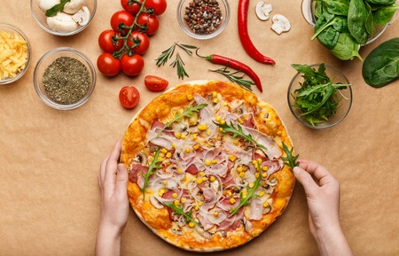 Homemade pizza. Woman adding rocket salad to pizza, decorating it, top view Archivio Fotografico