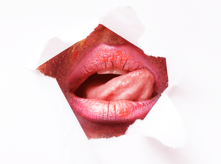 Intimate care and tenderness. Young woman erotically playing with tongue, licking her lips in paper hole, living coral tone