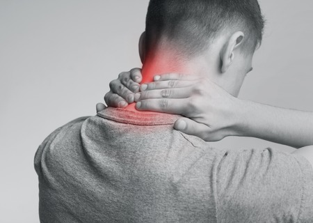 Young man with neck pain, massaging red injured zone, back view. Monochrome photo with red inflamed zone
