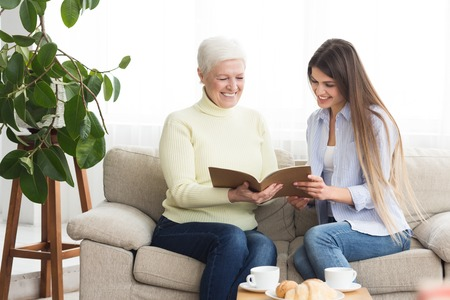 Senior woman and daughter looking at photos in album, having rest at home