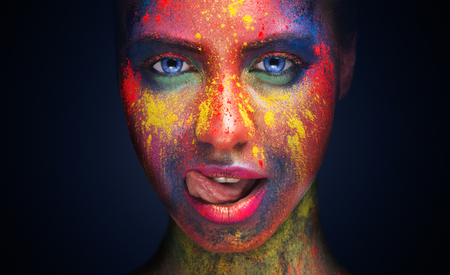 Seduction. Sensual woman with bright creative makeup licking her lips, looking erotically at camera, black background