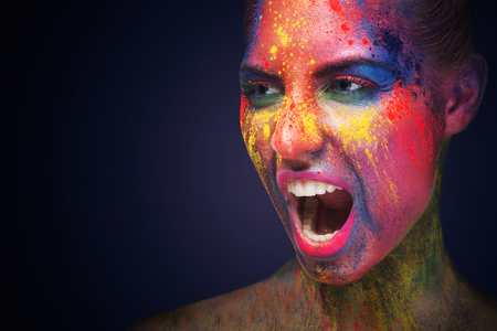 Emotional portrait of young girl with bright colorful makeup screaming at free space on dark studio background