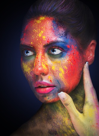 Cosmetics, make up, idea. Young woman with colorful artistic bodypaint, closeup portrait on black Stock Photo