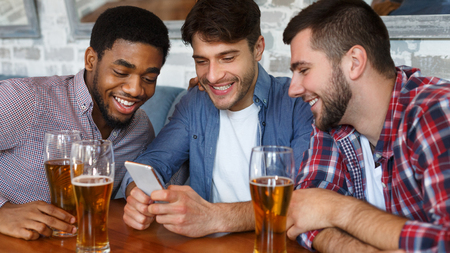 Friends having fun. Men using smartphone and drinking beer in bar Imagens