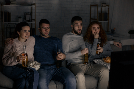Friends watching horror films, eating popcorn and drinking beer at home
