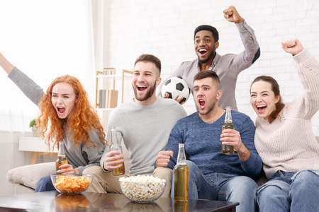 Group of friends watching football and celebrating victory at home 版權商用圖片 - 118952263